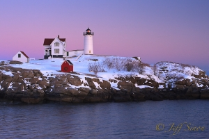 Nubble Light with a fresh blanket of snow under the pastel colors of the late day sky.
