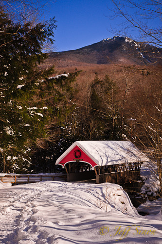 Covered bridge over the Pemigewasset River at the Flume Gorge covered in snow, mountains in the background.