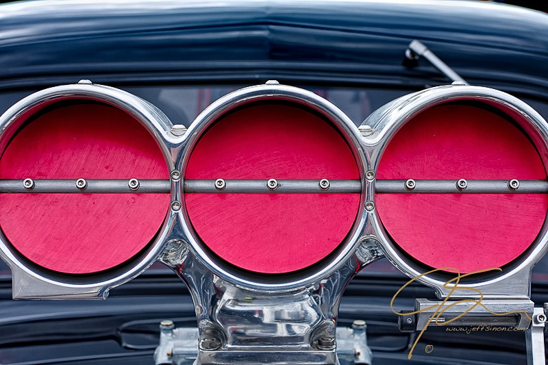 three circular throttle plates on a drag car hood scoop.