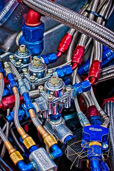 braided stainless steel hoses along with blue and red anodized fittings feed the engine of a drag racing car