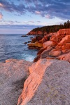 A large foreground granite boulder draws the eye towards the distant Otter Cliffs in Acadia National Park. The pink granite casts an orange glow as it is lit by the first rays of the morning sun in this vertical image.