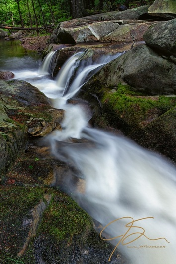 Long exposure, vertical photo of a small flume and triple waterfall on the Mad River in Farmington, NH.