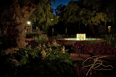 Night time, long exposure, photo of one of the three fountains found in Portsmouth, New Hampshire's Prescott Park gardens. A large tree frames the left side of the horizontal image, as the vibrant greenery and red flowers along the brick pathway lead around the fountain. A street light outside the garden gives a starburst of light in this night time scene.