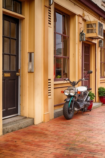 scooter parked on the brick sidewalk  in front of the yellow exterior of a State Street, Portsmouth, NH business..