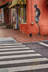 Street art painting of a girl with a black cat on her shoulders, painted on the red stucco exterior of an ice cream shop on State St. in Portsmouth, NH.