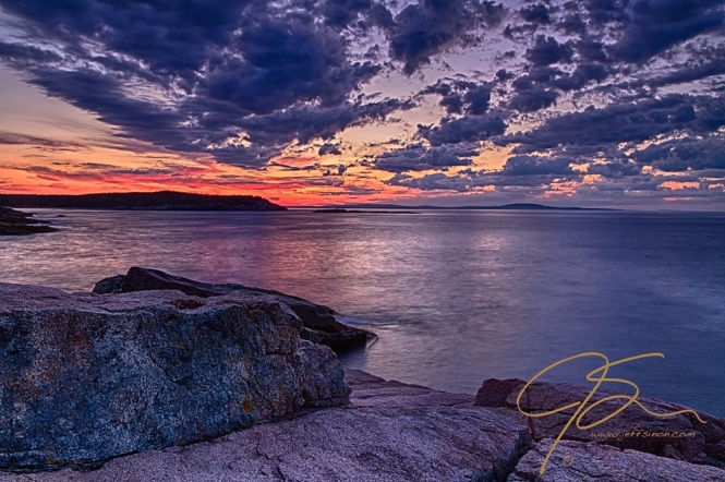 Granite ledge meets the Atlantic Ocean along the shore of Acadia National Park. Dramatic clouds lead the eye towards the orange-yellow brightening of the sky as the sun is about to crest the horizon.