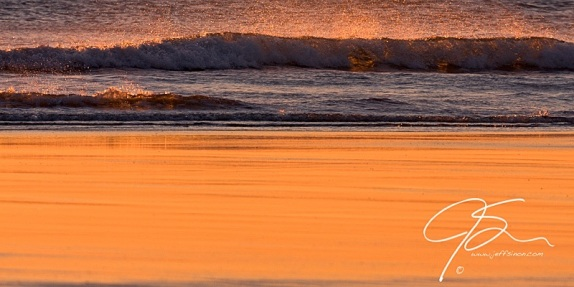 As the surf crashes onto the sand, the rising sun's golden light is reflected off of the wet beach sand. The spray from the waves glows like a thousand gold gems as they capture the sunlight.