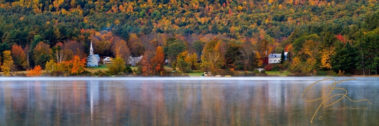 As the mist settle on the pond, a small white church sits nestled in the beautifully colored autumn foliage on the far shore. To the right in the image, also partially hidden in the trees, is a white farm house along side a bright red barn. Shot in Eaton, NH.