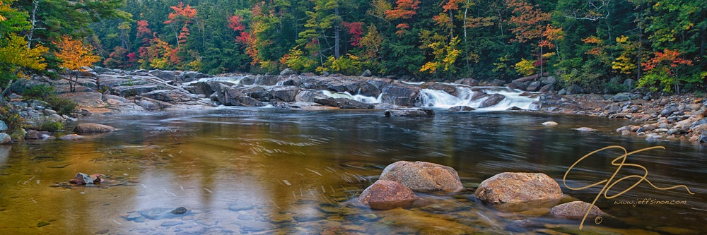 Panoramic image of Lower Falls on the Swift River, Kancamagus Highway, NH. Autumns vibrant colors line the far shore of the river, and upstream of the falls.