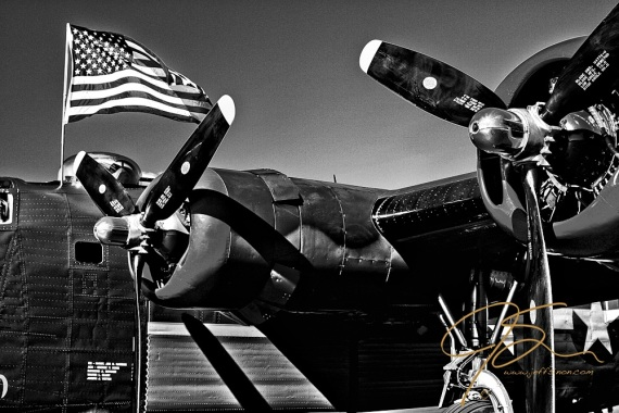 "Black and white photo of part of the left side of the B-24 Liberator ""Witchcraft."" Owned by the Collings Foundation, from Stow, Mass. Shown in the left side of the fuselage with part of the wing, with it's two powerful engines and part of the landing gear. The American flag flying proudly over the top gunners dome in the roof of the aircraft."