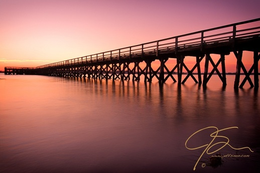 The long pier at Ft. Foster in Kittery, Maine, seems to vanish into the distance towards the setting sun. Long exposure giving the water below the pier a soft, dreamy look.