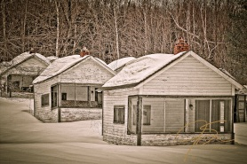 three little white rental cabins, one behind the other, nesteled in the snow. Their worn, bowed green roofs, with small brick chimenies, supporting a heavy load of snow. The green trim around the windows and doors much in need of a coat of paint. It has also been far too long since the white clapboard siding has felt the stroke of a paint brush.