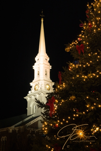 Night time photo of the north church in Portsmouth, NH. Vertical image of the well lit steeple in the background, and a nicely decorated Christmas tree in the foreground.