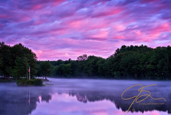 Mist covers the glass smooth water reflecting the clouds that are colored in shades of pink and purple from the rising sun. A small island image left, about a third of the way up frm the bottom has a flag pole with the U.S. flag on it. Among the shoreline trees on the point of land behind the island stands several photographers eagerly awaiting the launch of the hot air balloons at the 2010 Pittsfield, NH hot air balloon festival.