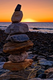 Neatly stacked, one atop the other, a rock cairn sitting among the boulders on the rocky coast at Rye Harbor. The sun is just about to peak above the horizon giving the cloudless sky a nice ogange glow