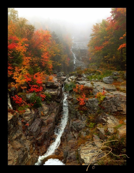 Silver Cascade in Crawford Notch State Park, NH, seems to originate in the clouds, as the upper falls is hidden in the mist from the low cloud cover on the rainy day this was shot. The sides of the falls in this vertical image are lined with the vibrant red, orange, and golden yellow of the peak autumn foliage. A black boarder surrounds the image that was captured with the Camera+ app on my iPhone 4S, enhanced, and then shared to facebook, without ever leaving the app.