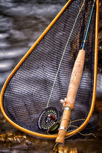 A Sage 1 weight fly rod with an Abel TR Light reel, leening up against a stream side rock, a wooden landing net as backdrop
