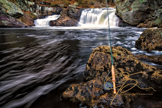 A Sage 1 weight fly rod with an Abel TR Light reel, leening up against a stream side rock, with a waterfall as background. Long exposure giving the water going over the falls a smooth, silky look.