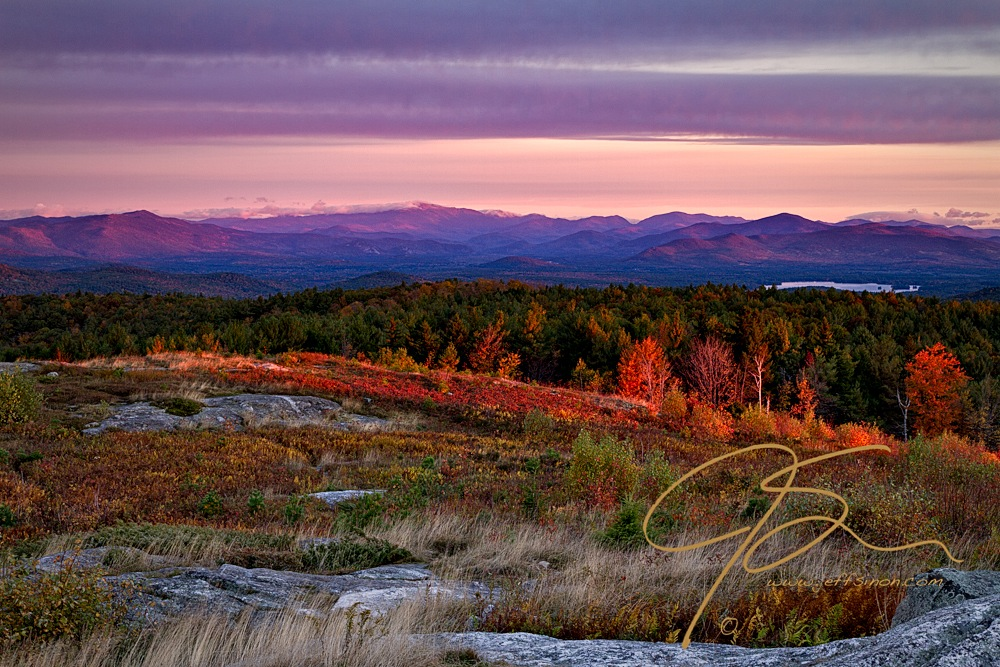 From the summit of Foss Mountain looking north towards the White Mountains. The summit of Mt. Washington, shrouded in clouds, can be seen in the distance. The eastern facing slopes of the mountains in the distance glow with the first rays of the rising sun.