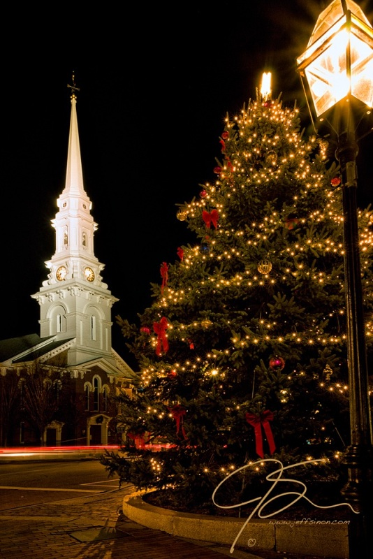 Night time scene depicting Market Square in Portsmouth, NH. A cast iron street lamp, a beautifully decorated Christmas tree, and the well lit steeple of the North Church are all in this vertical image.