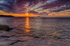 Sunrise over the granite shore at Acadia National Park. granite ledge in the foreground, the sun setting the morning clouds afire. The sun's reflection on the cold Atlantic waters leads like a beacon towards the horizon.