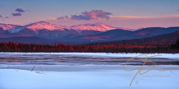 The Presidential Range, including Mt. Washington seen in late winter over a frozen Cherry Pond in the Pondicherry National Wildlife Refuge.