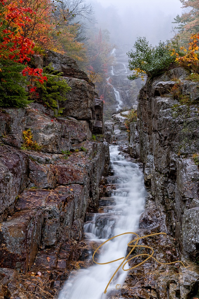 Vertical image looking from the base of Silver Cascade in Crawford Notch State Park, Crawford Notch, New Hampshire. Bright autumn foliage in red, yellow, and orange hues line both sides of this tall, narrow waterfall as it desends out of the mist.