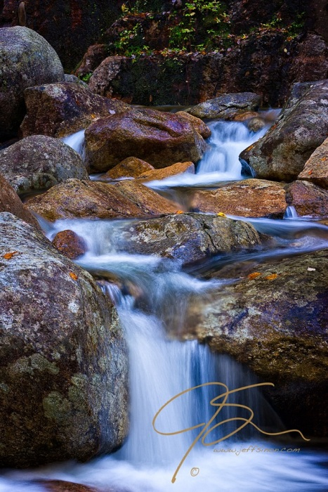 Long exposure of water cascading over large multi-colored boulders. Lush green leaves cling to the sheer wall of granite in the background. Vertical.