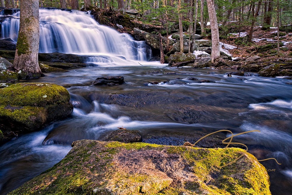 A large moss covered, sunlit rock dominates the foreground of this image of Tucker Brook falls. Remnants of a late April snow storm can be seen on the forest floor. A long exposure gives the water flowing over the falls in the left background a soft, silky look.