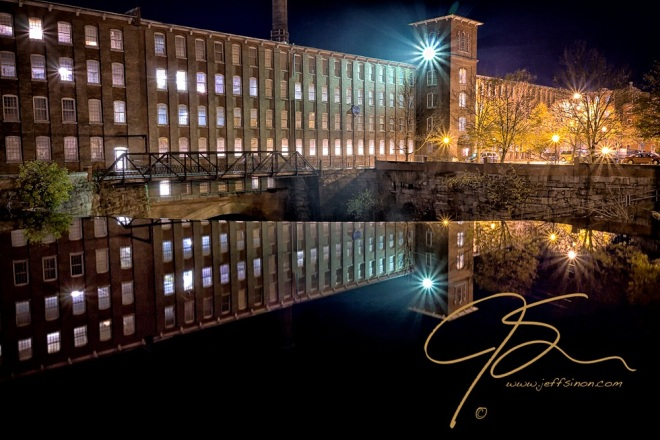 The Cocheco Mill Building in downtown Dover, NH. The bright blue-white spotlight on the tower shining brightly, a mirror image of the building reflected in the glass smooth water above the waterfalls. Numerous widows are lit from within in this long brick structure.