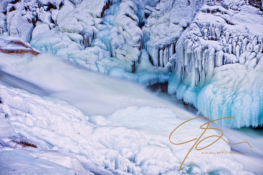 The frigid water at Livermore Falls flows between the beautifully patterned ice on the banks.