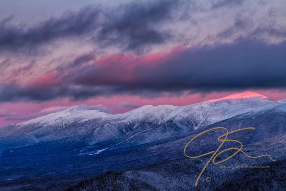 Alpenglow reaches the summit of Mount Washington, piercing through a gap in the clouds. The snowy peaks of the rest of the Presidential Range trailing off into the distance towards image left.