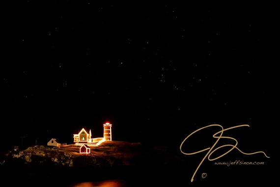 Nubble light decorated in Christmas lights under a star filled night sky. The constellation Orion can be seen just above and to the right of the lighthouse.