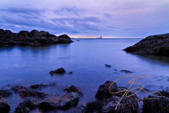 From low on the edge of a small, boulder and rock rimmed cove, looking out over the incoming tide towards Whaleback Lighthouse at the mouth of Portsmouth Harbor. Seaweed and barnacles cover the foreground rocks and the water of the incoming tide is given a smooth dreamy look by the long exposure.