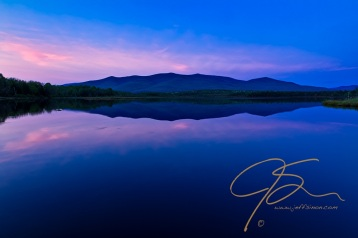 The last of the late day light causes the wispy clouds over Cherry Pond to take on a pinkish hue. The far off blue-green of the mountain range beyond the pond is reflected on the glassy smooth surface of the water.