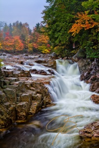 Vertical image of Rocky Gorge on the Swift River in the White Mountains of New Hampshire. Vibrant fall foliage can be seen on the far bank above the gorge.