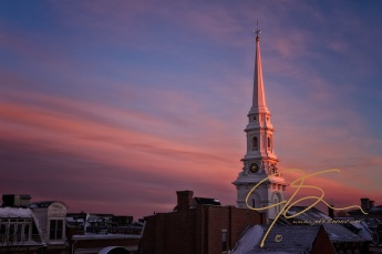 The steeple of the North Church in Portsmouth, NH stands tall above the downtown rooftops. The late day sun casting a beautiful pink-orange glow on both the church spire and the clouds in the sky. Hints of the seasons first major snowfall still cling to the many rooftops.
