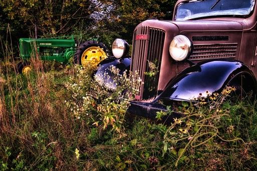 Antique John Deere tractor and GMC truck sitting among the tall weeds in a rural Maine field