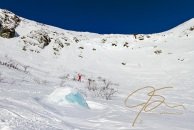 Standing dressed in my bright red winter hikng shell, in the vast bowl of Tuckerman Ravine, I'm dwarfed by the surrounding wall of snow.