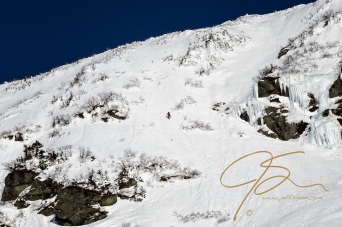 Lost among the exposed rock, a skier climbing the bowl in Tuckerman Ravine is dwarfed by his surroundings.