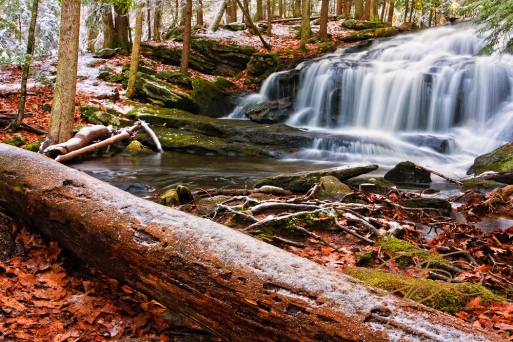 Captured just after the first dusting of snow, Tucker Brook Falls in Milford, NH. With a large snow frosted log dominating the foreground and the falls itself dominating the background in this dramatic forest scene.