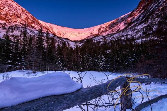 Looking out over frozen, snow covered Hermit Lake, the headwall and surrounding mountains of Tuckerman Ravine glow in the pink alpenglow as the first rays of the sun hit the snow covered slopes. In the foreground is the weathered cedar fence on the shore of the small lake.
