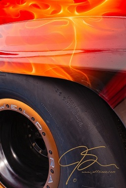 Close up of a racing slick and the expertly air brushed flames of a drag racing car.