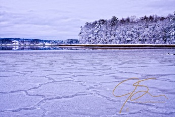 Intricate patterns are formed as the ice flows on the Bellamy River form a continuous sheet on the water's surface.