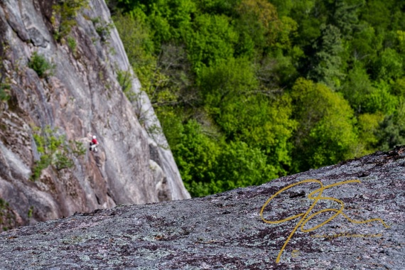 A rock climber dressed in a bright red shirt clings to the face of Cathedral Ledge.