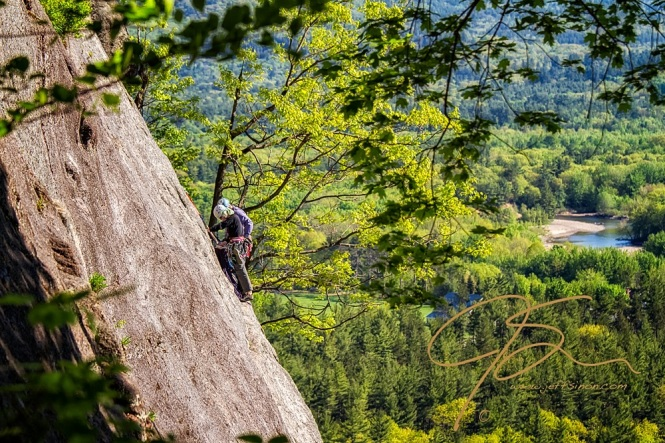 A man and woman pair of rock climbers perched on the face of Cathedral Ledge looking out over the Saco River and the valley 500 feet below.