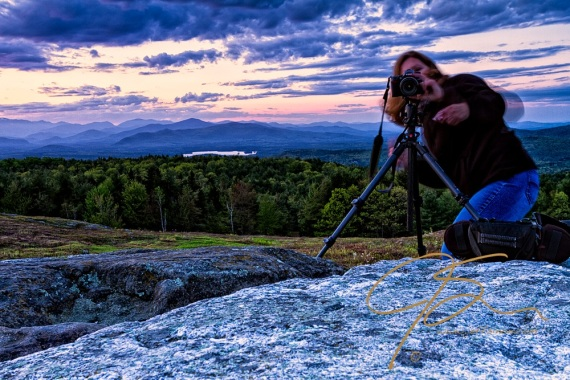 Photographer in motion. Tracy readies her camera to photograph me. All the while there is a beautiful scene under the setting sun behind her.