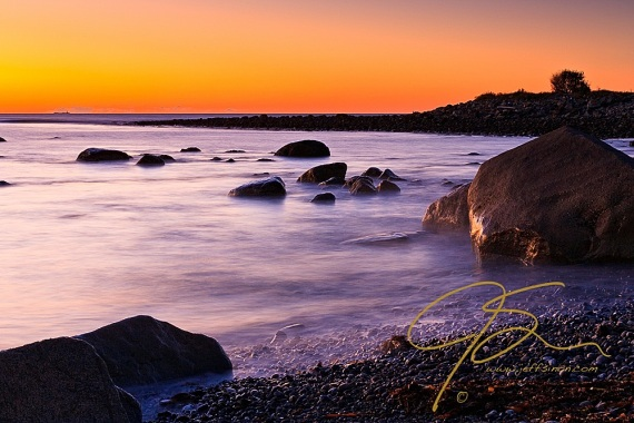 A golden sunrise at Rye Harbor State Park. A large granite boulder sits in the milky surf.
