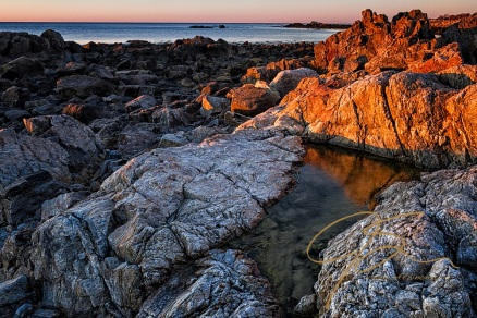 Golden light baths the rugged granite on the New Hampshire seacoast.