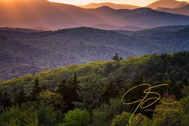 Golden sunlight shines down on the green covered mountain ridges